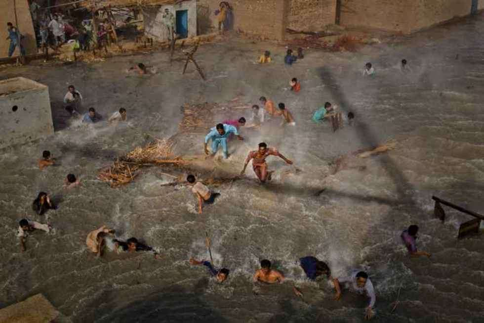 1st Prize People In The News Stories Pakistan floods, August-September: Flood victims scramble for food as they battle the downwash from a Pakistan army helicopter during relief operations, Dadu, Pakistan, 13 September.